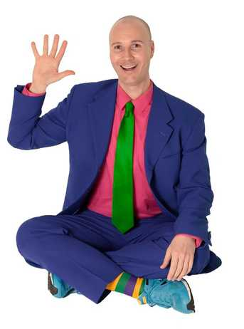 Christopher in a purple suit, hot pink shirt, green tie, yellow/purple/green striped socks, and blue sneakers. He is waving while sitting cross-legged and smiling.
