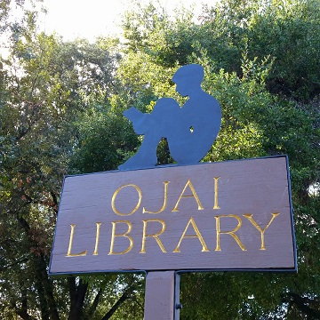 The Ojai Library sign features a silhouette of a young boy reading.