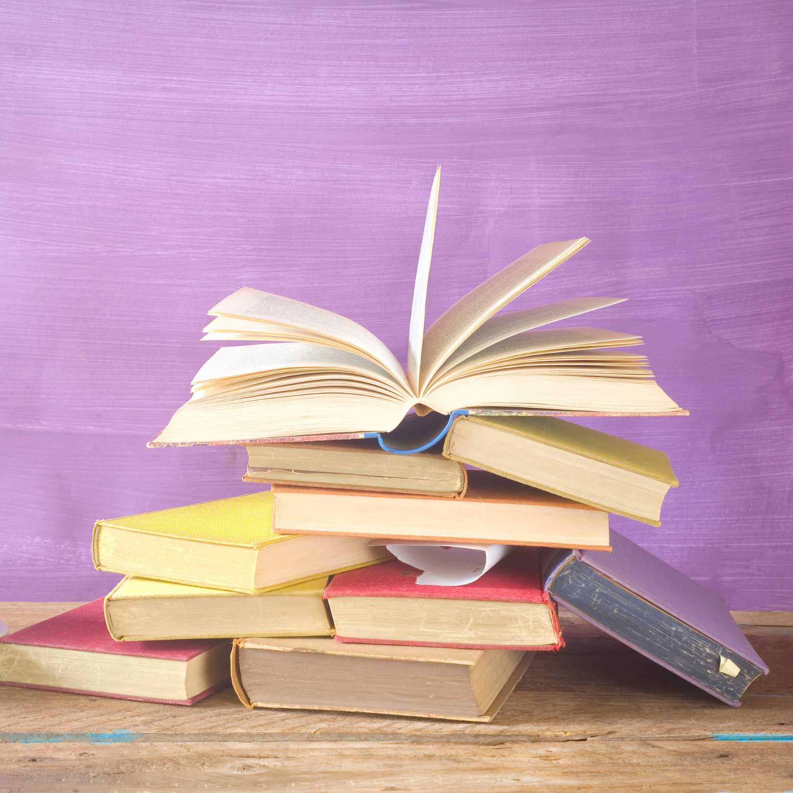 Purple background with desk stacked with colorful books