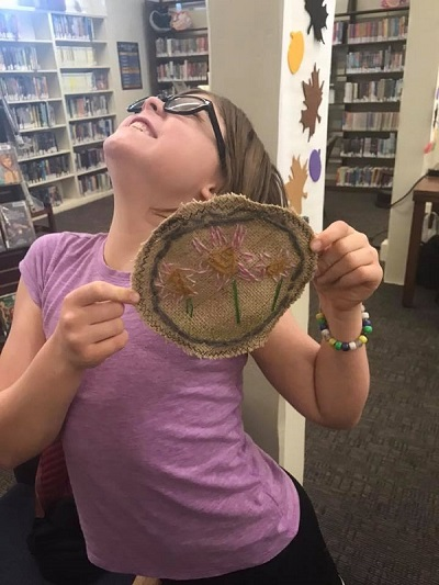 Child showing off her embroidery in library