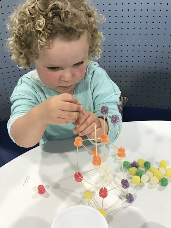 Picture of little girl making a structure from gumdrops and toothpicks