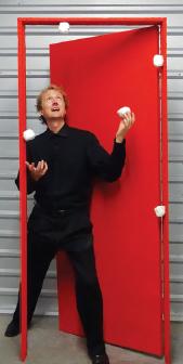 David Cousin standing in a red door way juggling