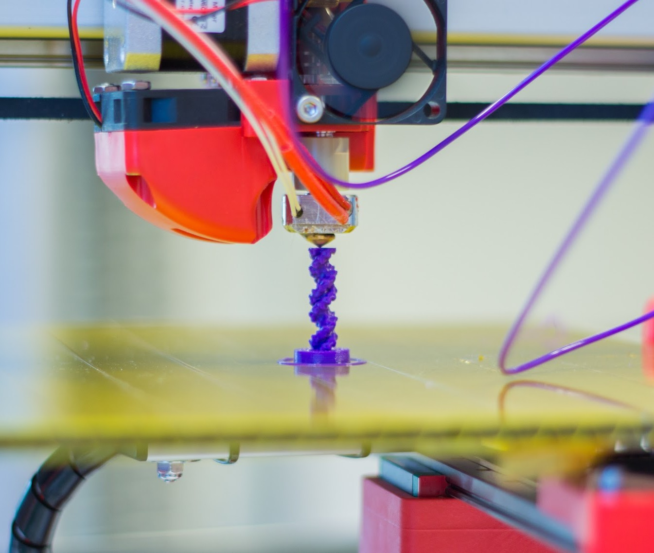 Photo of a 3D pinter printing something purple.