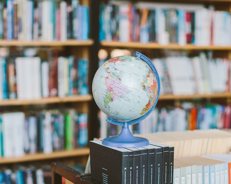 A globe in front of a library book shelf