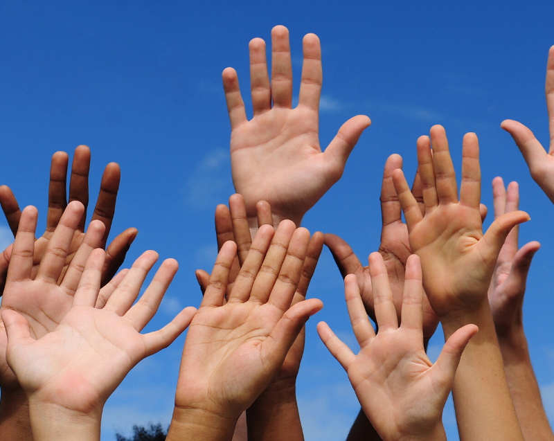 Photo of many hands raised in the air