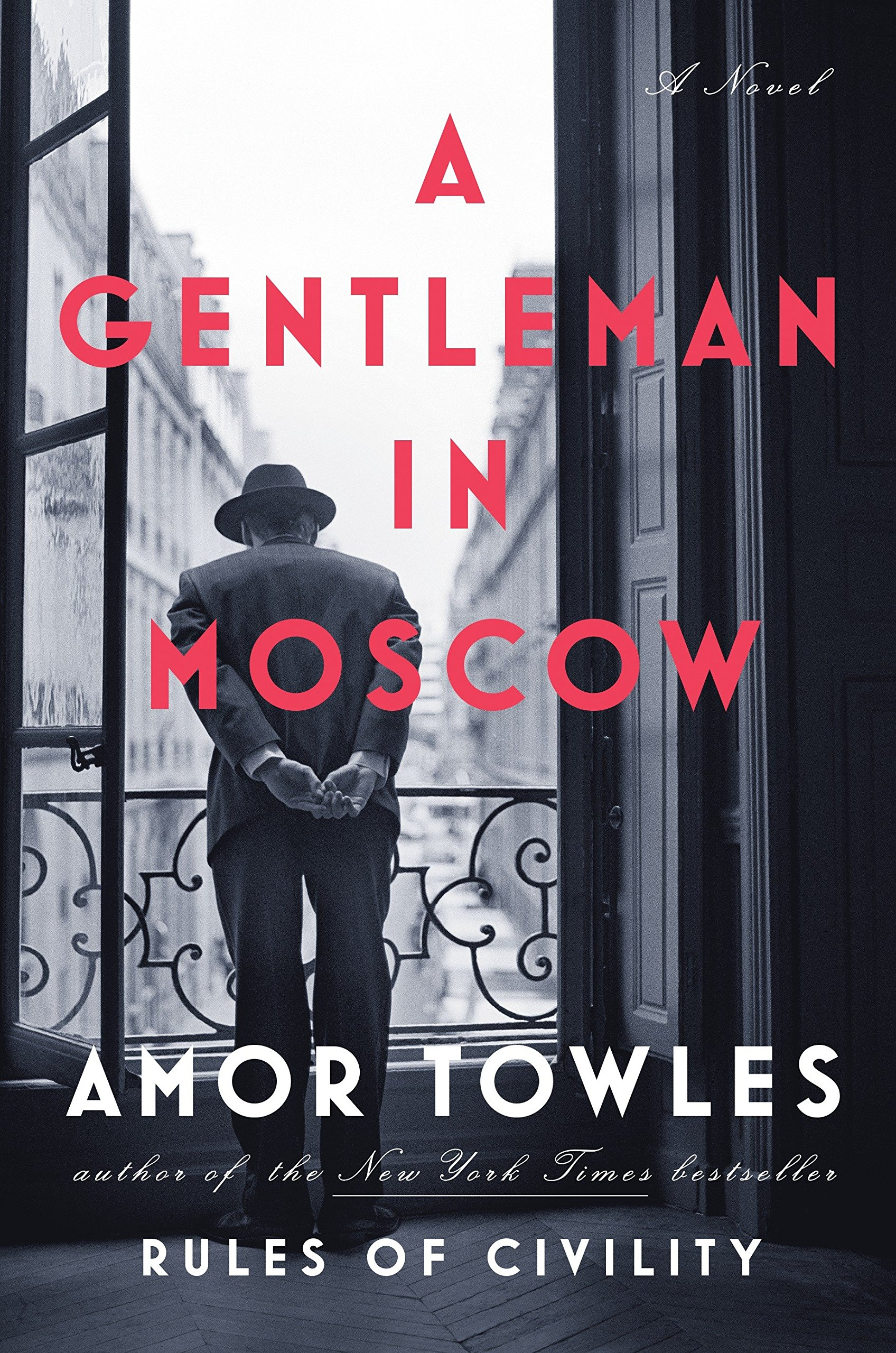 book cover for a gentleman in moscow - black and white photo of a man in a hat looking down from a balcony.
