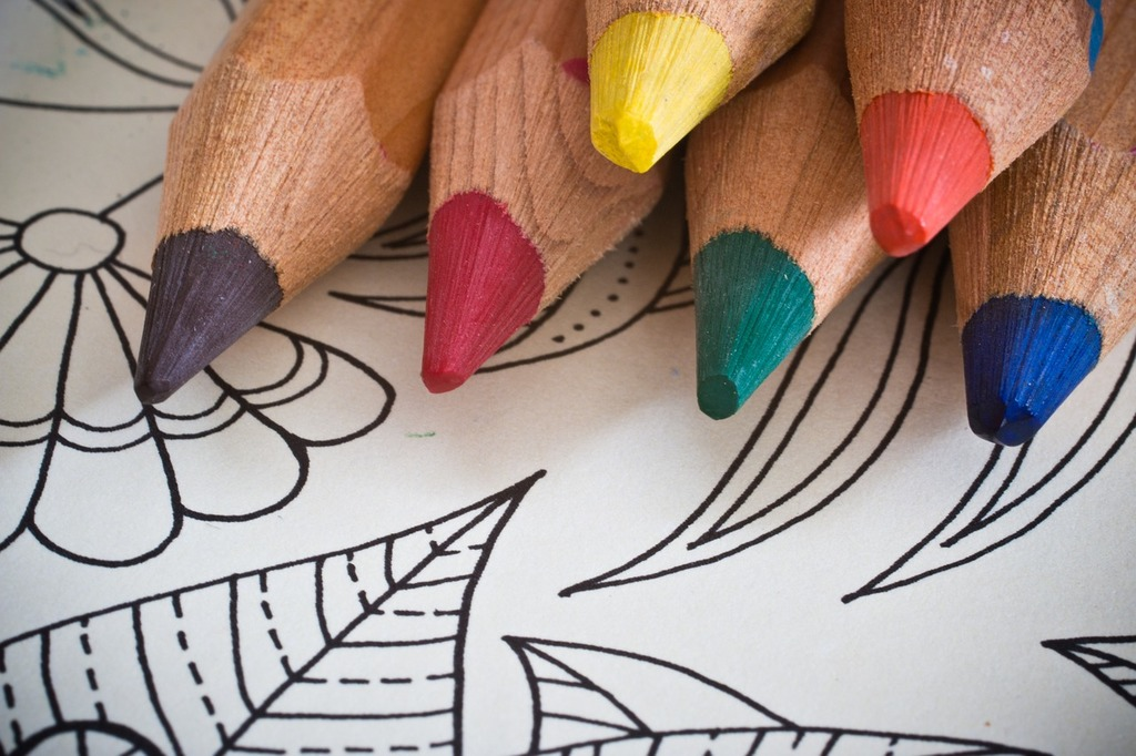 six sharpened colored pencils sit on top of a blank coloring page