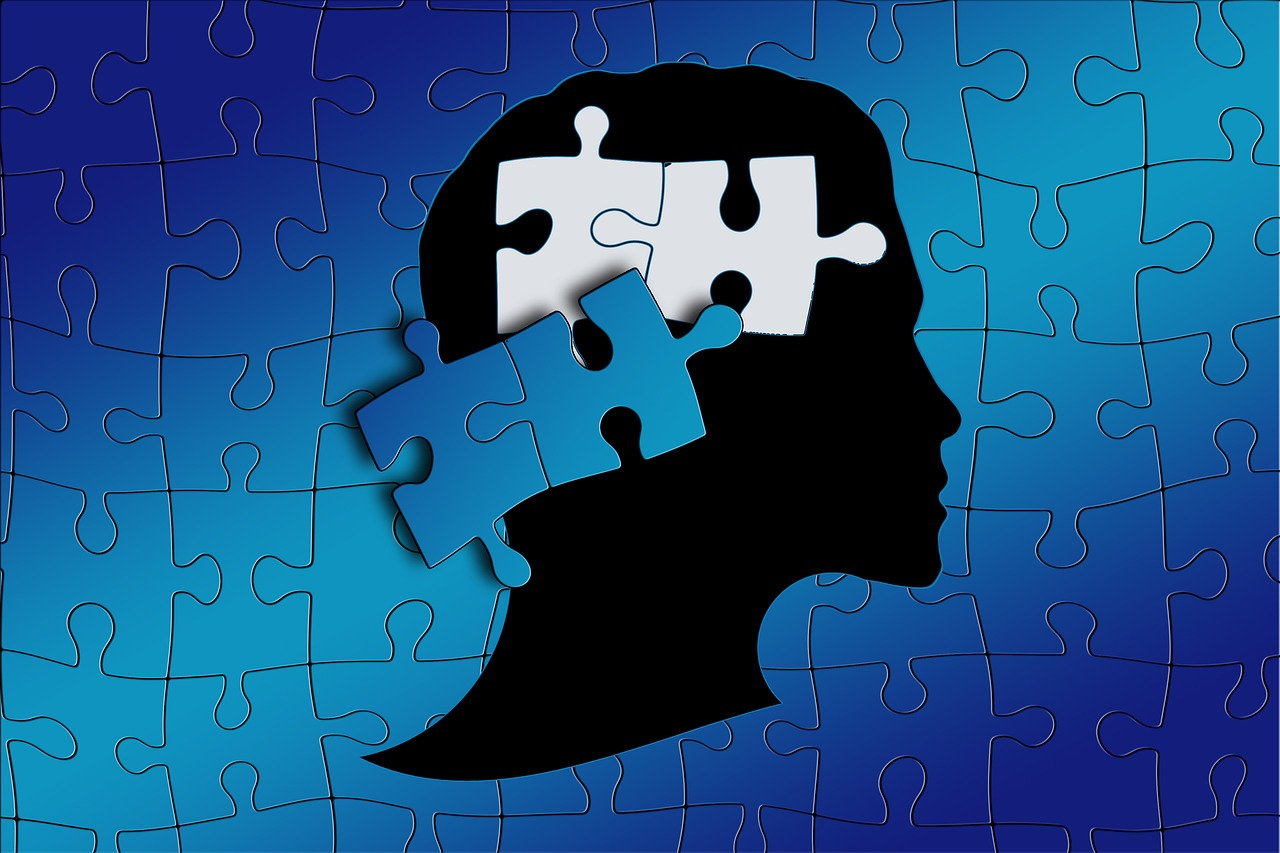 blue puzzle pieces scattered over outline of a person's head
