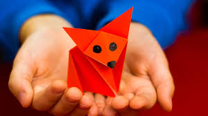 A child's hands holding a red fox made out of origami
