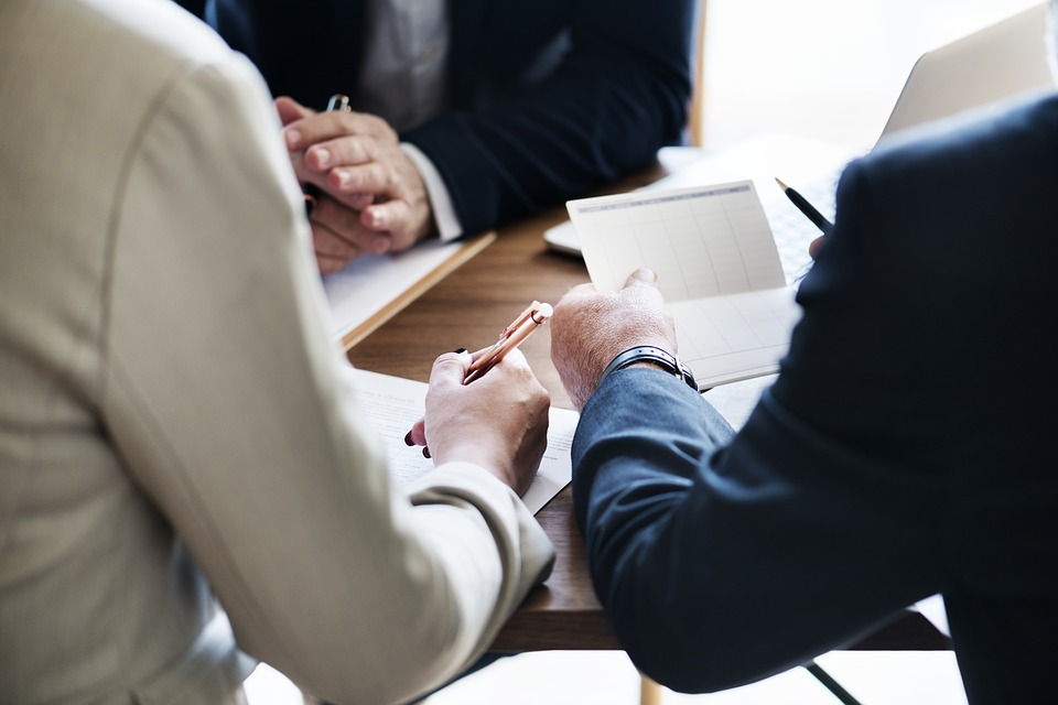 image depicts hands holding documents, presumably in a meeting