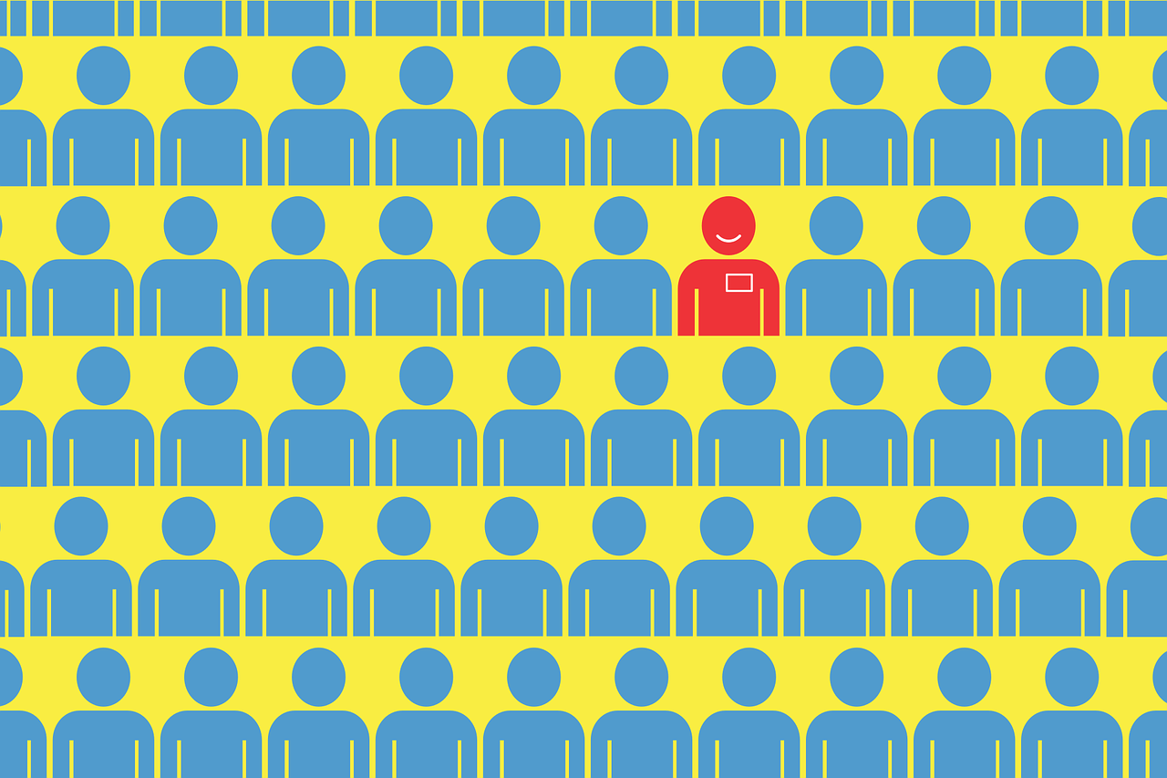 image shows many rows of blue people icons and one red person icon with a smile amidst the crowd of mundanity