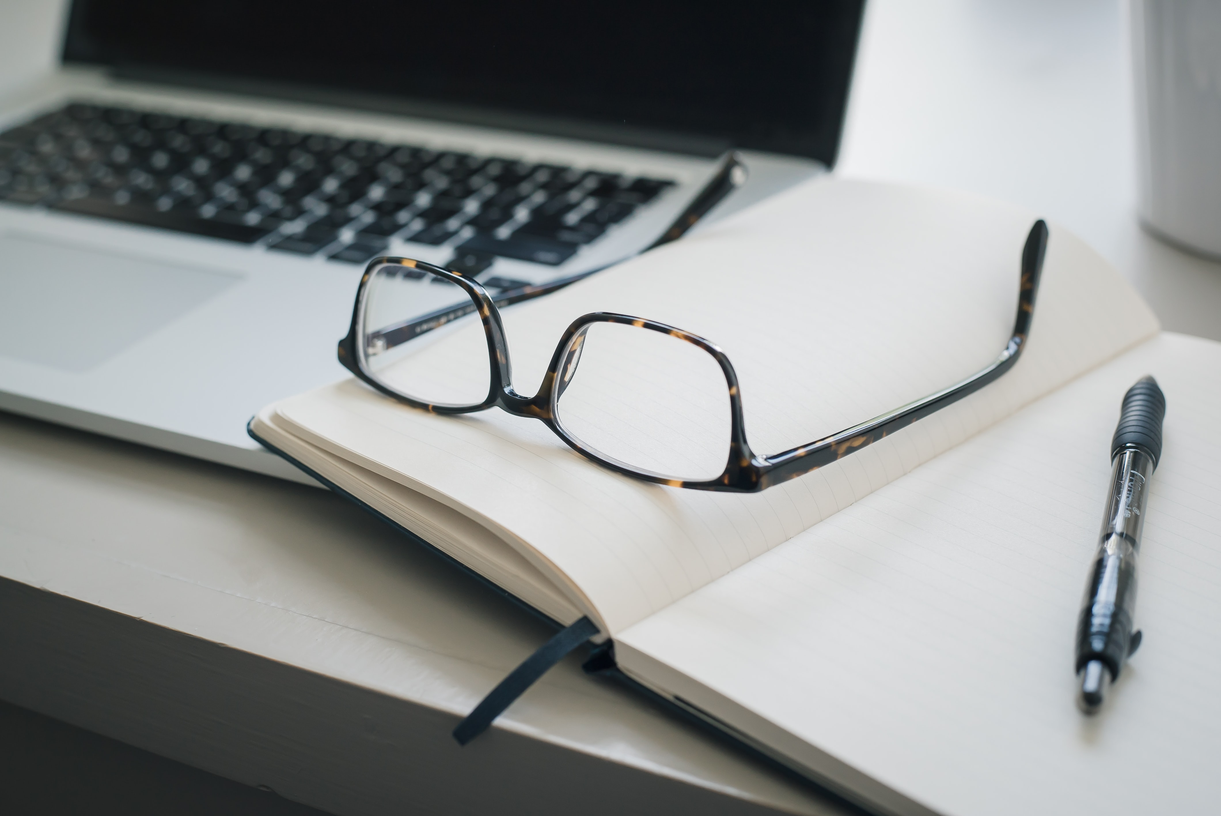 glasses and pen on a book resting atop a keyboard - photo by Trent Erwin on Unsplash