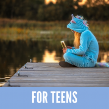 Girl in a blue unicorn jumpsuit sitting on a dock reading
