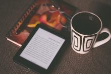 Picture of coffee and eReader on table